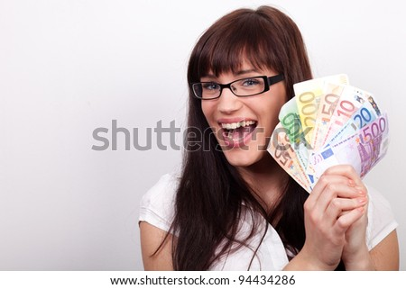 Ecstatic young woman with her hands full of money - stock photo