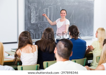 Ecxited student gives answer near blackboard during lesson - stock photo