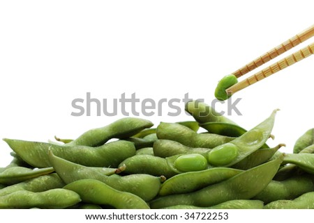 Edamame with shuck removed and the pod held with wooden chopsticks, isolated on white with copyspace - stock photo