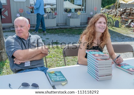 EDEN MILLS, ON - SEPTEMBER 16:  Canadian writers, Ian Hamilton and Carrie Snyder, sign their books at the annual Writers Festival in Eden Mills, Ontario on September 16, 2012. - stock photo