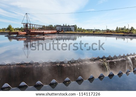 Edge of sedimentation reservoir with clean water overflowing - stock photo
