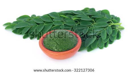 Edible moringa leaves with ground paste over white background - stock photo