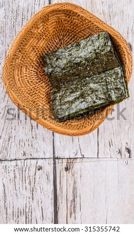 Edible seaweed or Nori in Japanese language in wicker bowl over wooden background