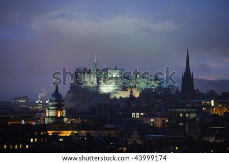 Edinburgh Castle, Scotland, at dusk in winter from the East.  On the left is the dome of the Talbot Rice Gallery (the public art gallery of The University of Edinburgh) and on the right the Hub. - stock photo