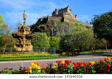 Edinburgh Castle view from Princes Street Gardens with fountain and flowers - stock photo