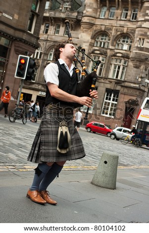 EDINBURGH-JULY 8,2009: Edinburgh street bagpiper on Royal Mile, Edinburgh, Scotland July 08, 2009. The bagpipe players are one of the symbols of Scotland. - stock photo