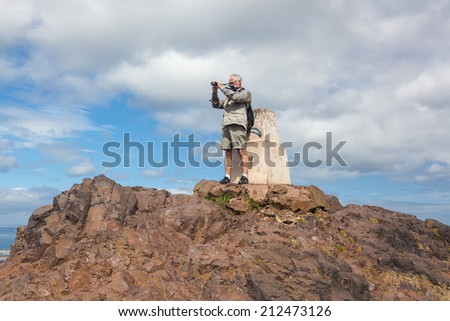 EDINBURGH, SCOTLAND: AUGUST 4, 2014: Elderly tourist taking photos from the Arthur's seat in Holyrood Park. Arthur's seat is popular destination for hiking and enjoying nature.  - stock photo