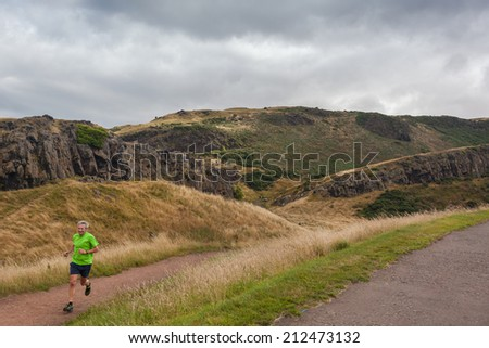EDINBURGH, SCOTLAND: AUGUST 4, 2014: Man jogging in Holyrood Park. Park's highest point Arthur's seat is popular destination for hiking and enjoying nature.  - stock photo