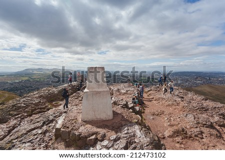 EDINBURGH, SCOTLAND: AUGUST 4, 2014: Tourists around viewpoint stone at Arthur's seat in Holyrood Park. Arthur's seat is popular destination for hiking and enjoying nature.