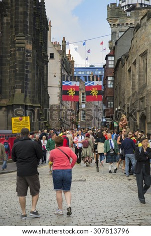 EDINBURGH, SCOTLAND - AUGUST 17, 2015:   Tourists walking in Edinburgh during the fringe festival the largest festival in the world.  Only the crowd and building in focus. - stock photo
