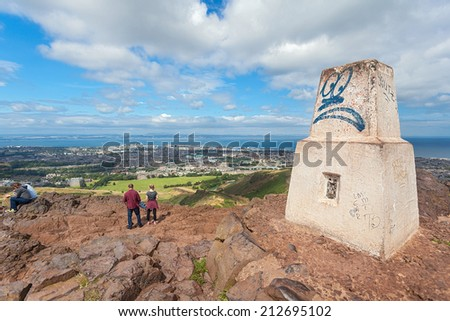 EDINBURGH, SCOTLAND: AUGUST 4, 2014: Viewpoint stone at Arthur's seat in Holyrood Park. Arthur's seat is popular destination for hiking and enjoying nature.  - stock photo
