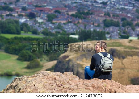 EDINBURGH, SCOTLAND: AUGUST 4, 2014: Young man  enjoying the view from the Arthur's seat in Holyrood Park. Arthur's seat is popular destination for hiking and enjoying nature.  - stock photo