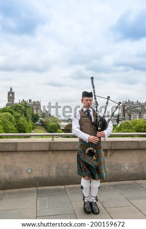 EDINBURGH, SCOTLAND - June 1,2014: Scottish Bagpiper playing his bagpipe on June 1, 2014 in Edinburg, Scotland - the most popular tourist city destination in Scotland. - stock photo