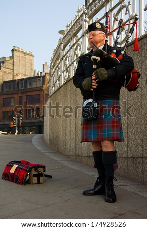 EDINBURGH, SCOTLAND, - MARCH 4: Unidentified Scottish Bagpiper playing music with bagpipe at Edinburgh on March 4, 2010. Edinburgh, the most popular tourist city destination in Scotland  - stock photo