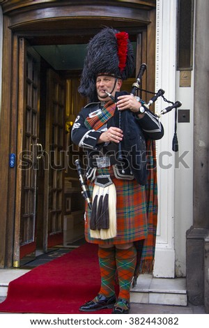 EDINBURGH, SCOTLAND, - MARCH 6: Unidentified Scottish Bagpiper playing music with bagpipe at Edinburgh on March 6, 2010. Edinburgh, the most popular tourist city destination in Scotland  - stock photo