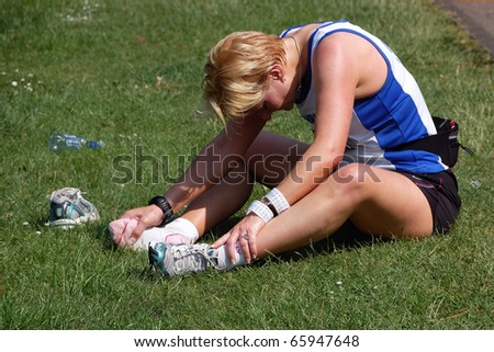 EDINBURGH, SCOTLAND, UK - MAY 23: Unidentified woman finishes the Edinburgh Marathon on the route, May 23, 2010 in Edinburgh, UK. Runner sits on the grass and investigates her injured leg.