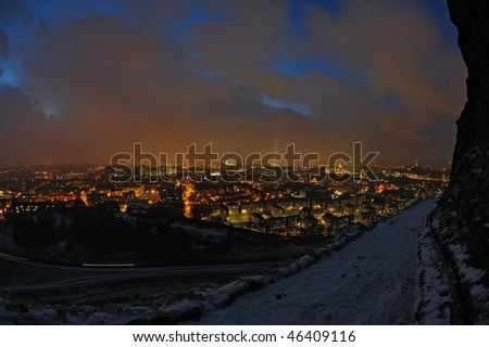 Edinburgh, Scotland, UK, skyline at night in winter with a moody sky.  It is snowing in the distance. - stock photo