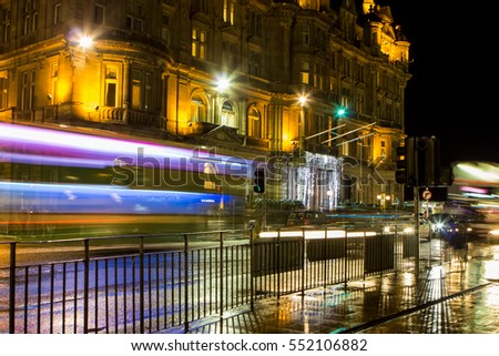 EDINBURGH, UK - DEC 22, 2016: Motion blurred buses on Princess Street with Christmas lights reflecting in rainy road