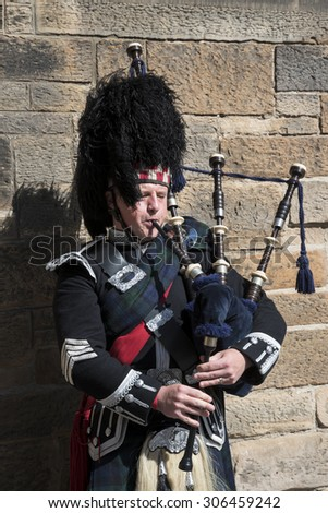 Edinburgh 08/06/2015: visiting Edinburgh people can see street artist that on the old streets of the town plays pipe with the typical vest of Sctland. They give the tight atmosphere of the town . - stock photo