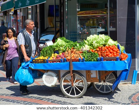EDIRNE, TUKKEY, 02.04.2016: Man of Turks seller of fruits and vegetables from its large wagon with the goods on the streets of the city of Edirne in Turkey. View to crowded street with shops