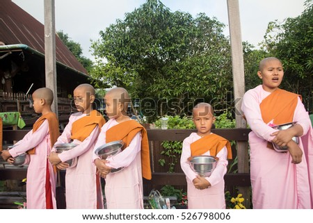 Editorial use only: NOV20,2016  Nuns were standing on the wooden bridge for receive food in Sangkhla Buri District, Kanchanaburi,Thailand, Religious ceremonies in the traditional Buddhist. Little nuns