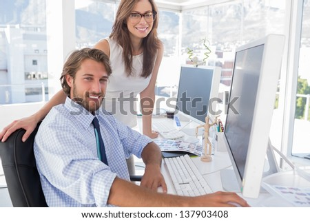 Editors smiling at the camera at their desk in modern office