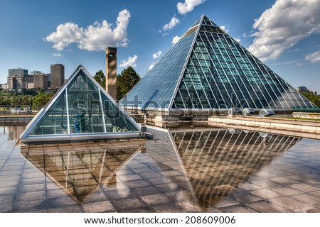 EDMONTON, AB, CANADA - JULY 8: The Muttart Conservatory stands against the Edmonton skyline July 8, 2014. The buildings' glass pyramids are one of Edmonton's most famous icons built in 1976. - stock photo