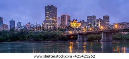 EDMONTON, CANADA - MAY 20: Panorama of Edmonton's skyline  at dusk on May 20, 2016 in Edmonton, Alberta. The Saskatchewan River is in the foreground and a traffic bridge is on the right. - stock photo