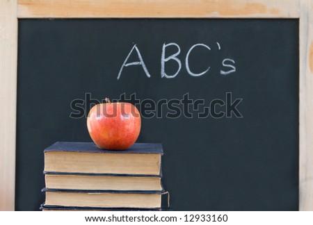 "Education: ""ABC's"" written on chalkboard with apple & books - stock photo"