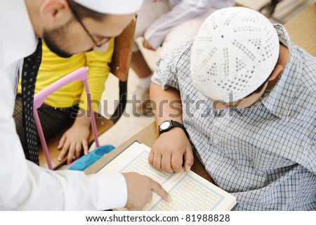 Education activities in classroom at school, Muslim teacher showing Koran to kid - stock photo