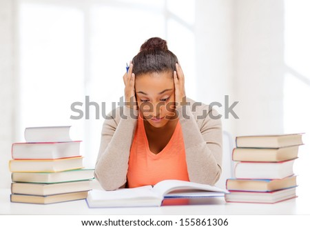 education and business concept - tired student with pile of books and notes studying indoors - stock photo