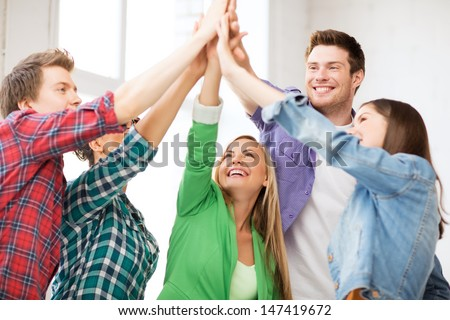 education and friendship concept - happy students giving high five at school - stock photo