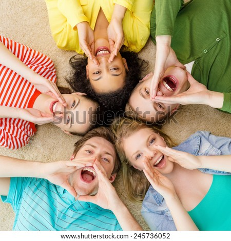 education and happiness concept - group of young smiling people lying down on floor in circle screaming and shouting - stock photo