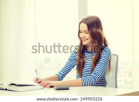 education and home concept - happy smiling student girl with notebook, calculator and book - stock photo