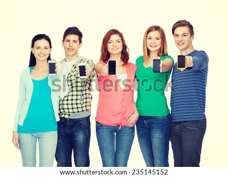 education and modern technology concept - smiling students showing blank smartphones screens - stock photo