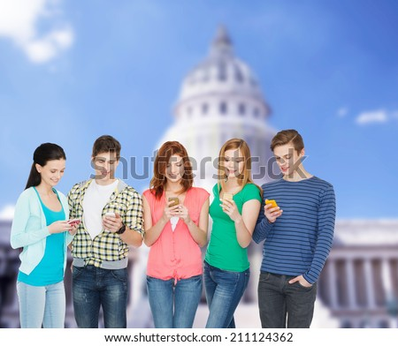 education and modern technology concept - smiling students with smartphones - stock photo