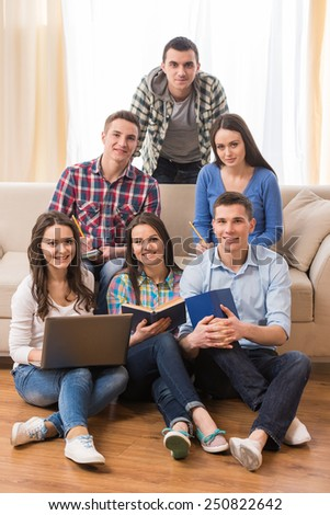 Education and people concept. Group of students are sitting on sofa and on the floor with laptop and books. - stock photo