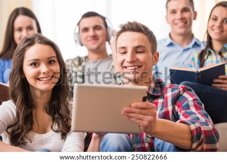 Education and people concept. Group of students with tablet, are looking at the camera while sitting in room. - stock photo