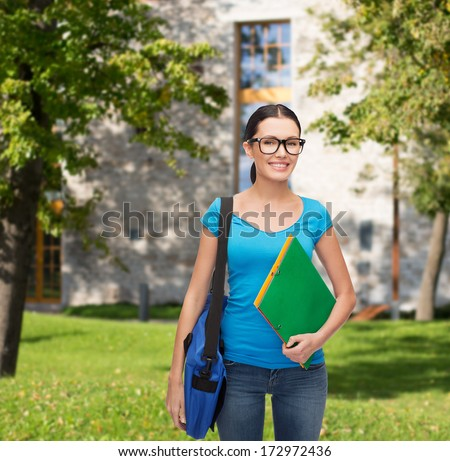 education and people concept - smiling student in eyeglasses with bag and folders standing