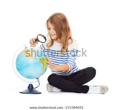 education and school concept - little student girl looking at globe with magnifier - stock photo