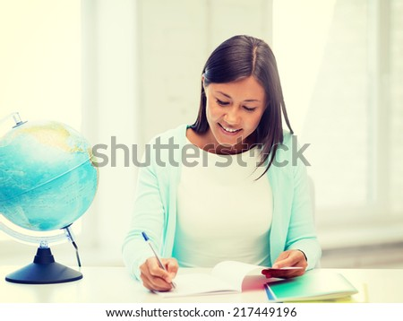 education and school, travel concept - female teacher with globe and notepad - stock photo