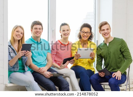 education and technology concept - smiling students with tablet pc computer at school - stock photo
