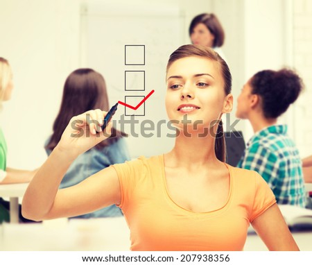 education and technology concept - student drawing checkmark on virtual screen - stock photo