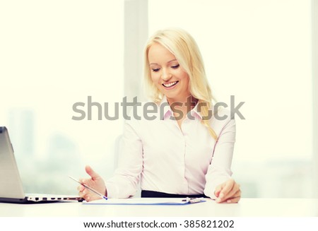 education, business and technology concept - smiling businesswoman or student with laptop computer and papers sitting in office - stock photo