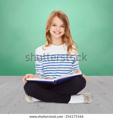 education, childhood, people and school concept - little student girl studying and reading book over green chalk board background - stock photo
