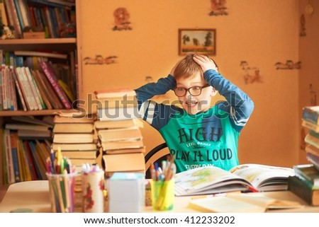 education, childhood, people, homework and school concept - bored student boy reading book or textbook at home - stock photo