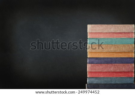 Education concept. A tall stack of books piled up on right side of frame in front of black chalkboard which provides copy space. - stock photo