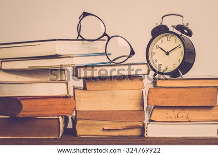 Education concept. Alarm clock with old books and eyeglasses on table . Vintage filter - stock photo
