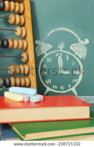 Education concept. Books, abacus, chalk and chalk drawing of alarm clock - stock photo