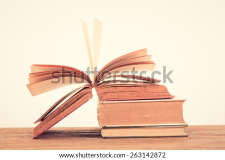 Education concept. Eyeglasses with Alarm clock with old books on table . Vintage filter - stock photo